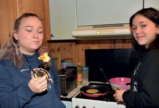 KOSER SEG: Her har søstrene laget lapper på kjøkkenet. Ruth-Margrethe prøvesmaker – mens lillesøster Linnea Kristine ser på.